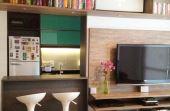 Prateleiras, TV na parede, banquetas e uma cozinha americana integrada deixam as coisas mais práticas